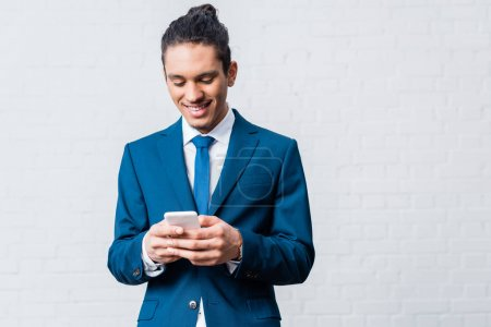 Photo for African american businessman using smartphone on white wall background - Royalty Free Image