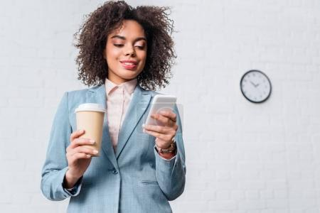 African american businesswoman holding coffee cup and using smartphone