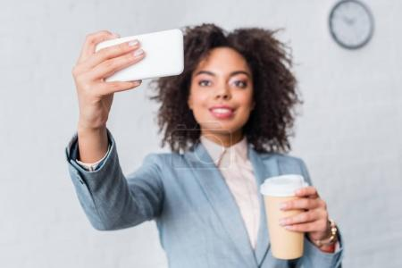 Businesswoman in suit holding coffee cup and taking selfie