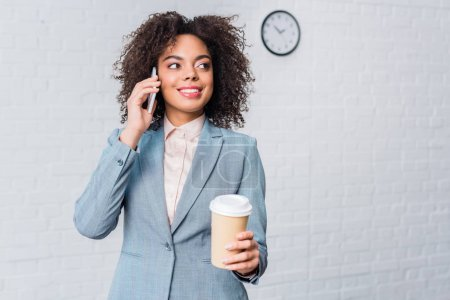 African american businesswoman with coffee cup talking on phone