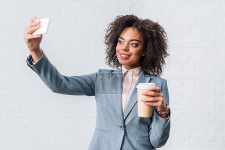 Photo for Young businesswoman with coffee cup taking selfie - Royalty Free Image