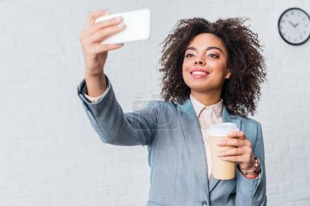 African american businesswoman with coffee cup taking selfie