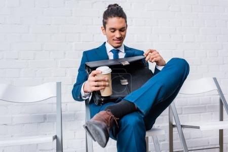 Photo pour Homme d'affaires assis sur la chaise et en attente avec la tasse de café et porte-documents en mains - image libre de droit