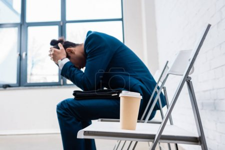 Stressed businessman sitting on chair by coffee cup