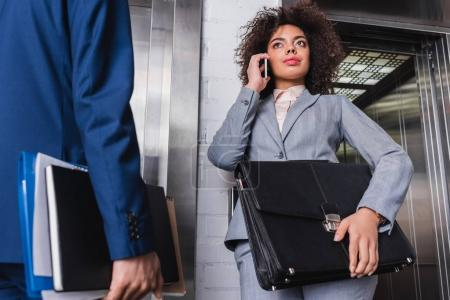Businesswoman with briefcase talking on the phone next to man by elevator