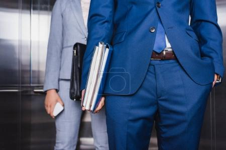 Cropped view of businessman with folders and woman with briefcase riding an elevator