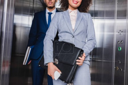 Cropped view of businesswoman with briefcase and man with folders standing in elevator