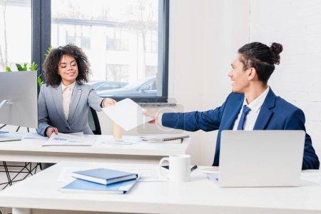 Photo pour Homme d'affaires, transmettre des documents à son collègue féminine par table de travail - image libre de droit