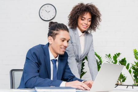 Businesswoman looking at man working on laptop in office
