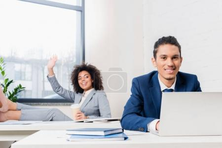 Businesswoman with paper cup greeting someone by businessman working on laptop in office