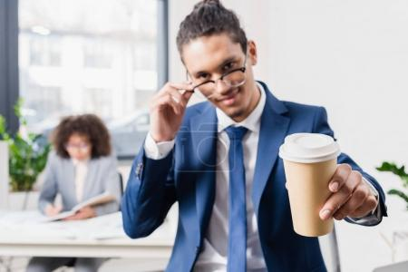 Smiling businessman offering coffee in paper cup