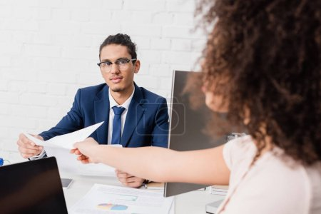 Businesswoman passing documents to her male colleague by working table