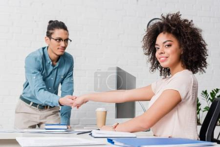 Businesswoman shaking hand of man by table with computer