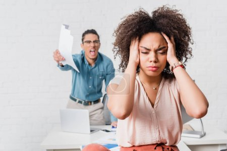 Woman suffering from stress because of angry male colleague in office