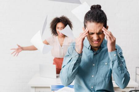 Businessman suffering from headache while his female colleague yelling in office