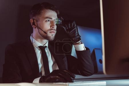 portrait of hacker with headset looking at computer screen at table in dark