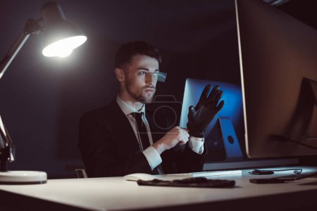 portrait of hacker wearing gloves while looking at computer screen at table in dark