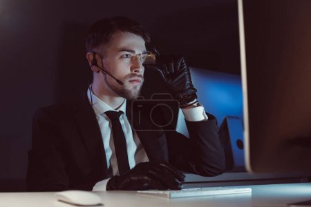 portrait of spy agent with headset looking at computer screen at table in dark