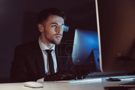 Photo pour Portrait de l'agent espion dans des gants tapant et regardant l'écran d'ordinateur à la table dans l'obscurité - image libre de droit