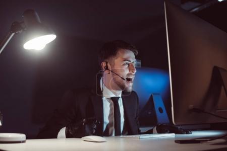 Photo pour Agent émotionnel avec casque hurlant tout en regardant l'écran de l'ordinateur dans l'obscurité - image libre de droit
