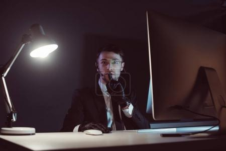 Photo for Portrait of spy agent showing silence sign at table with computer screen in dark - Royalty Free Image