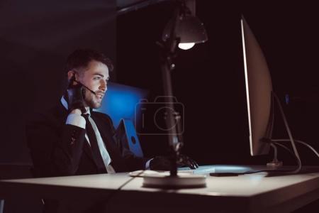 Photo pour Agent espion dans des gants avec casque assis à table dans l'obscurité - image libre de droit