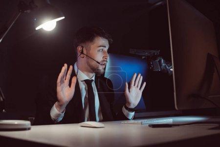 Photo pour Agent avec arme à feu à la tête et les mains en l'air assis à table avec écran d'ordinateur dans l'obscurité - image libre de droit