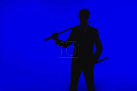 toned picture of silhouette of agent in suit with Katana