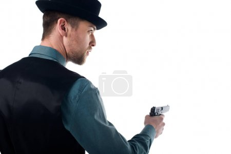 back view of spy agent in hat with gun in hand isolated on white