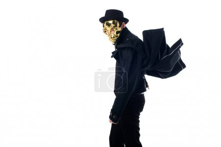 side view of criminal in mask, hat and black coat isolated on white