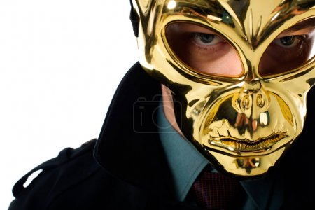 portrait of criminal in golden mask and black coat looking at camera isolated on white