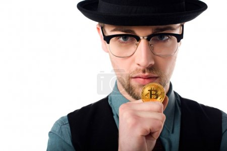 Portrait of spy in eyeglasses and hat holding golden bitcoin isolated on white