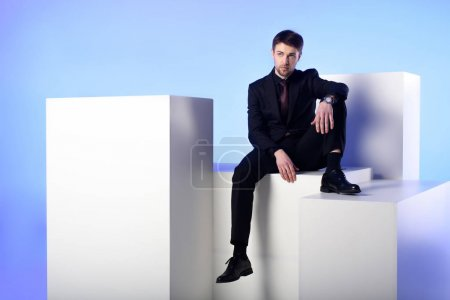 businessman in black suit sitting on white block isolated on blue