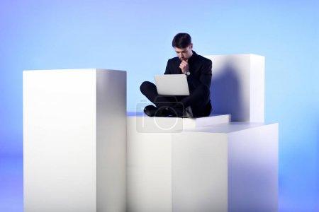 Photo pour Homme d'affaires utilisant un ordinateur portable tout en étant assis sur bloc blanc isolé sur blanc - image libre de droit