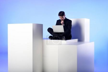 businessman using laptop while sitting on white block isolated on white