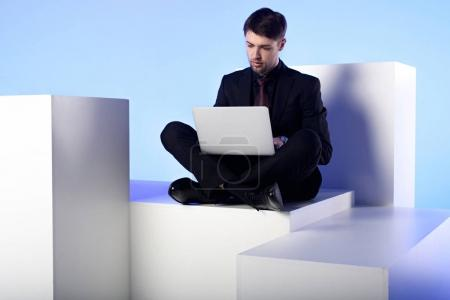 businessman using laptop while sitting on white block isolated on white
