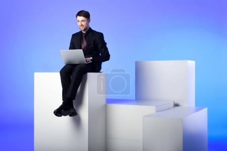 smiling businessman with laptop sitting on white block isolated on white