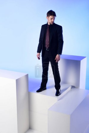 businessman in black suit standing on white block isolated on blue