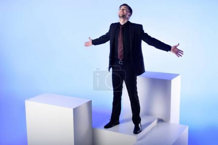 Photo pour Businessman in black suit with outstretched arms standing on white block isolated on blue - image libre de droit