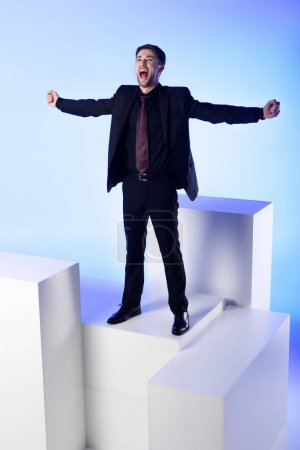 businessman in black suit with outstretched arms standing on white block isolated on blue