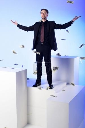 smiling businessman in suit standing on white block with falling dollar banknotes around isolated on white