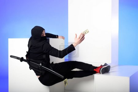 ninja in black clothing catching dollar banknotes on white blocks isolated on blue