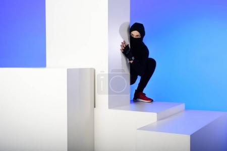 ninja in black clothing hiding behind white block isolated on blue