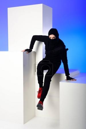 ninja in black clothing with katana behind getting across on white block isolated on blue