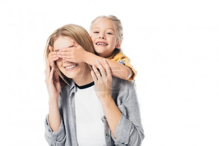 portrait of adorable kid covering mothers eyes to surprise her isolated on white