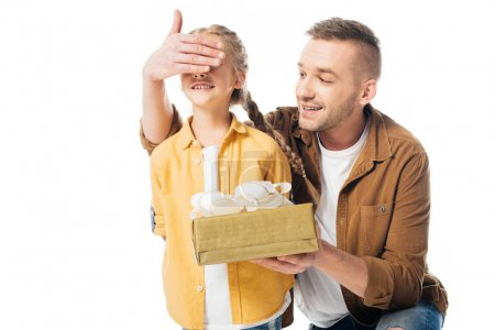 portrait of father with wrapped gift covering daughters eyes to surprise her isolated on white