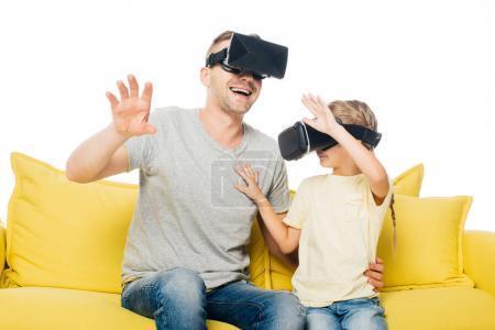 Photo pour Père et fille en réalité virtuelle écouteurs sur canapé jaune isolé sur blanc - image libre de droit