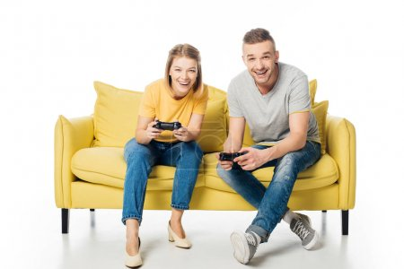 cheerful couple with joysticks playing video game while sitting together on yellow sofa, isolated on white