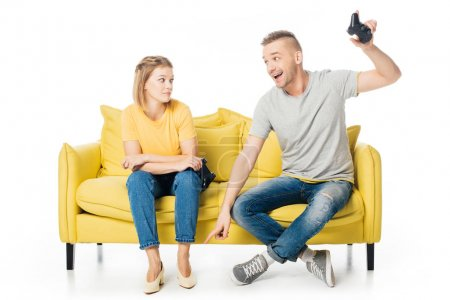 couple on yellow sofa playing video game together isolated on white