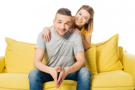 portrait of happy wife hugging husband on yellow sofa isolated on white